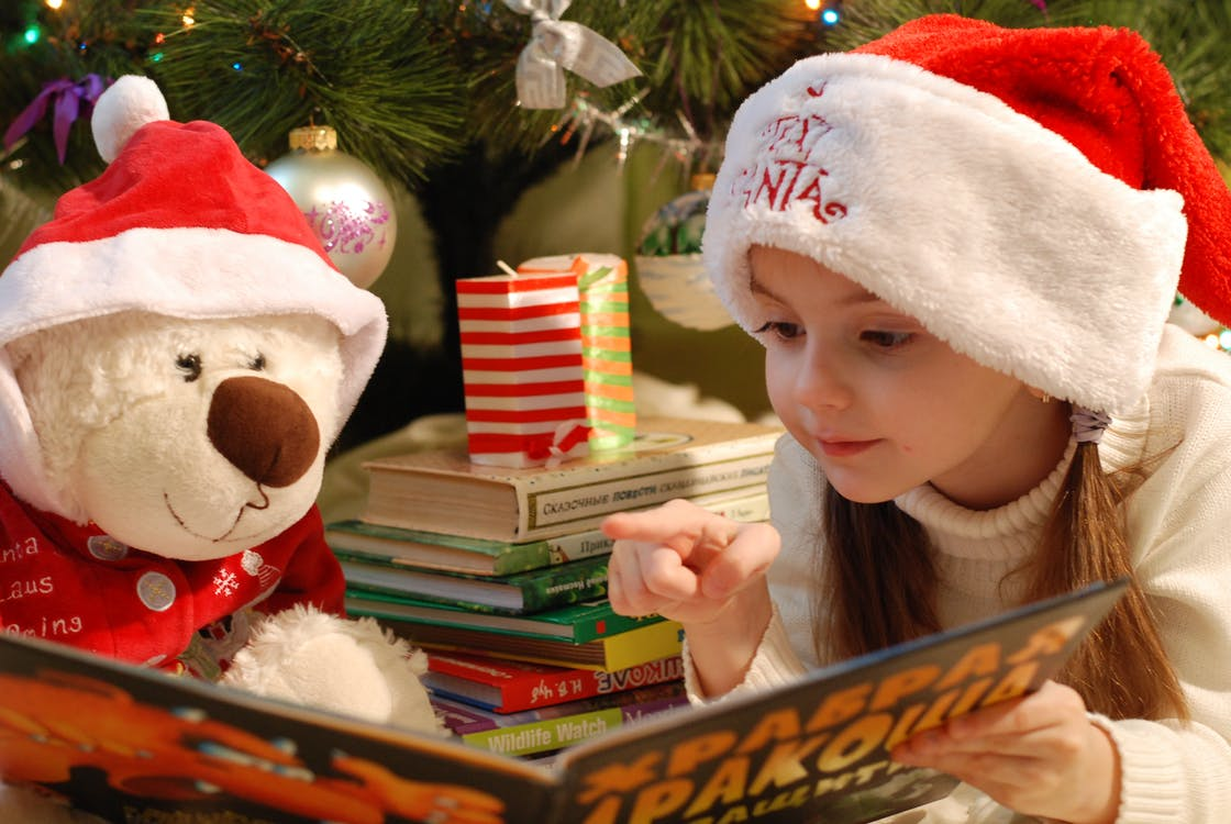 Child reading to her bear at Christmas, illustrating storytelling in IFA marketing ideas